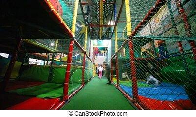 Children run on a labyrinth in big playroom of childrens club