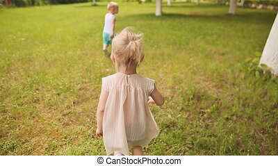 Children run through the grass and at the end fall