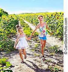 Children running across sunflower field outdoor. - Group...