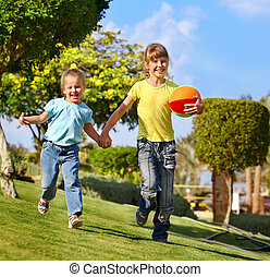 Children running in park. - Children running with ball in...