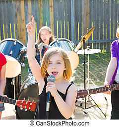 children singer girl singing playing live band in backyard...
