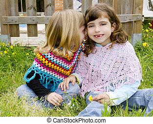 children sister girls whisper in ear meadow spring fence...