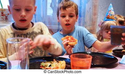 children sit around table, celebrating birthday party