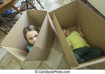 Children sit in cardboard boxes.