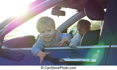 children sit in the car and play