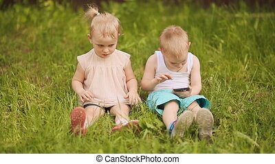 Children sit on the grass. The kid does not give the girl the phone.