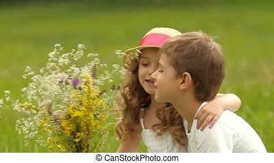 Children sit on the lawn in the park and sniff freshly harvested field flowers. Slow motion