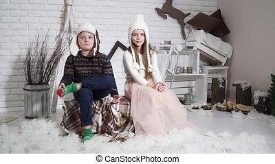 Children sit pose for the camera in the studio
