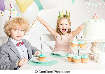 Children sitting at birthday table