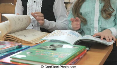 Children sitting at desk flips pages of book