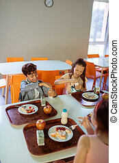 Children sitting at the table with trays of food while having lunch