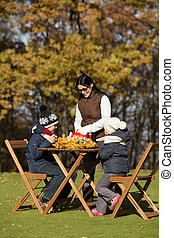 Children sitting at the wooden table on a picnic