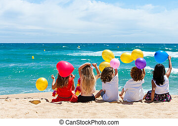 Children sitting on beach with color balloons. - Young kids ...