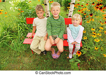 Children sitting on bench in garden