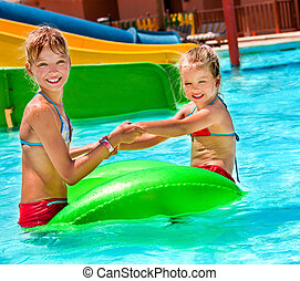 Children sitting on inflatable ring.