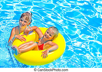 Children sitting on inflatable ring in water.