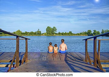 Children sitting on pier. Three children of different age - teenager boy, elementary age boy and preschool girl sitting on a wooden pier. Summer and childhood concept. Children on bench at the lake