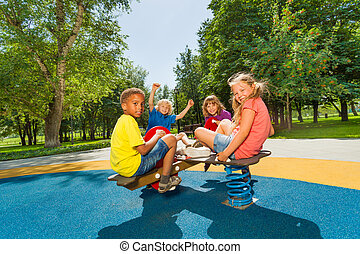 Children sitting on playground carousel together
