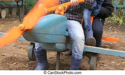Children sitting on the toy layout blue plane - Unidentified...