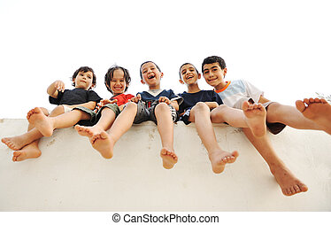 Children sitting on wall, happy boys laughing