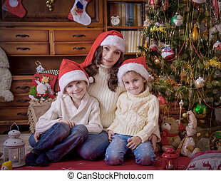 Children sitting with mother under Christmas tree in hats