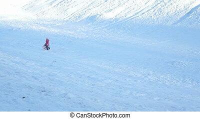 Children sledding downhill on a sunny winter day - Little...