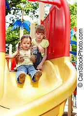Children slide on playground.