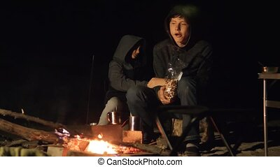 children smile kids drink tea teen sit by the fire at night...