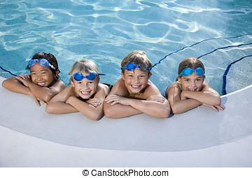 Children smiling at edge of swimming pool - Multi-ethnic...