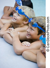 Children smiling, hanging on side of swimming pool