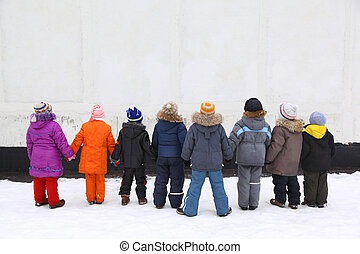 Children stand having joined hands, back view, wall for text