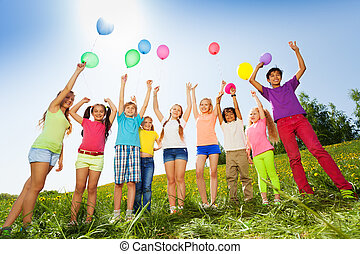 Children standing with arms up to flying balloons in green field