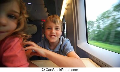 Children stare into camera lens on train, get in each other...