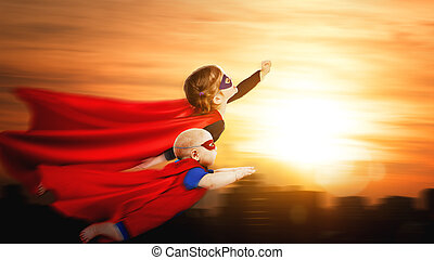 children superheroes flying across sunset sky. boy and girl...