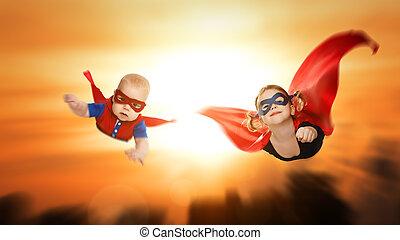 children superheroes flying across sunset sky. boy and girl...