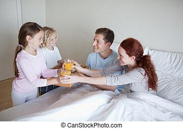 Children surprising their parents with breakfast