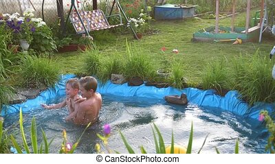 Children swim in a small lake on a hot summer day. Garden,...