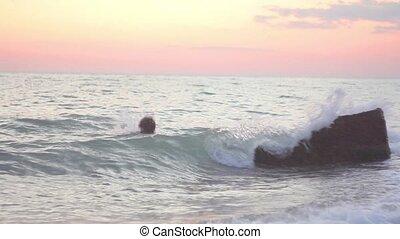 Children swim in the sea at night