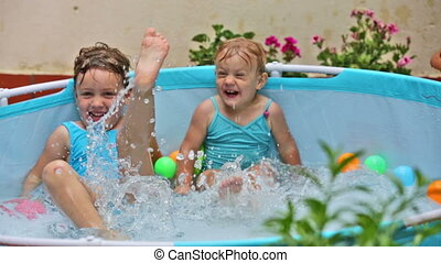 children swimming in kid pool - Happy children swimming in...