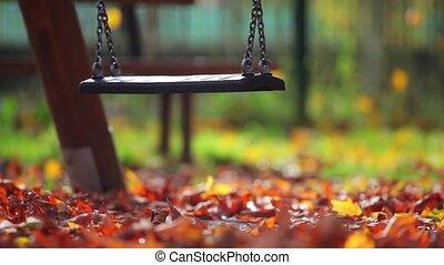 Children swing in the park swinging, autumn day