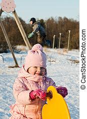 Children swinging on a swing in winter