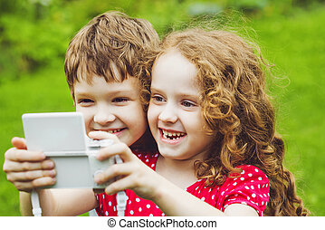 Children taking selfie with photo camera.