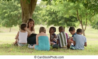 Children and education, young woman at work as school educator reading book to boys and girls in park