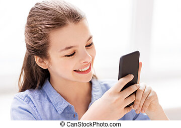 smiling girl messaging on smartphone at home