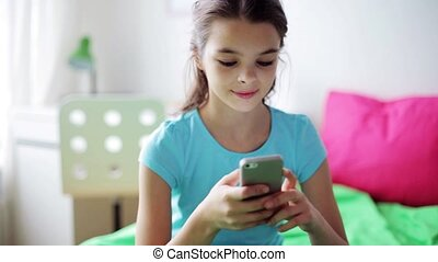 smiling girl texting on smartphone at home
