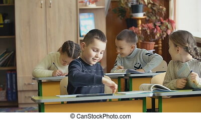 children tell ear secrets while sitting at the school desk