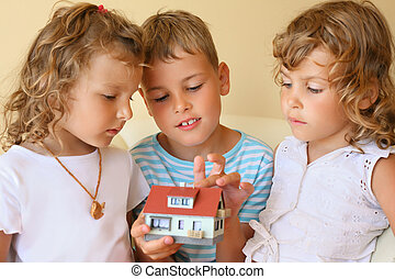 children three together keeping in hands model of house in cosy room, boy touches house finger