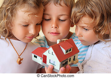 children three together keeping in hands model of house in cosy room