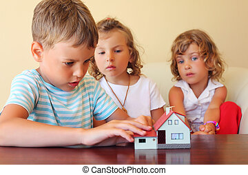 children three together looking at model of house standing on table in cosy room