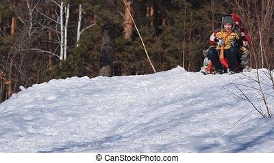 Children tobogganing - Three little children riding sledge...